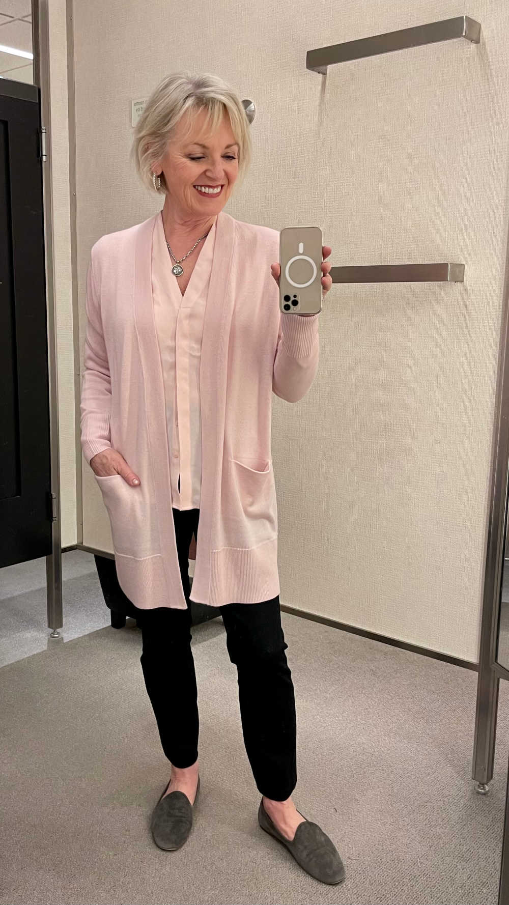 woman in dressing room wearing pink sweater with black pants