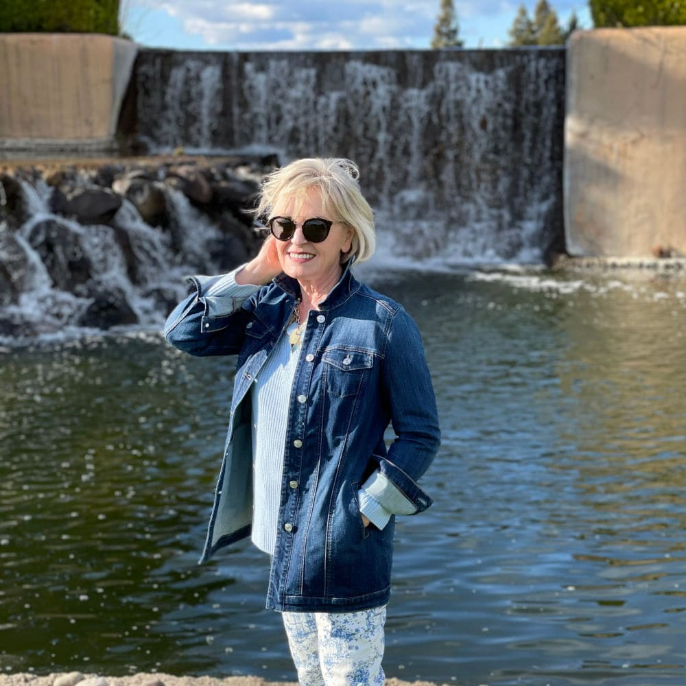 woman standing in front of waterfall wearing denim jacket