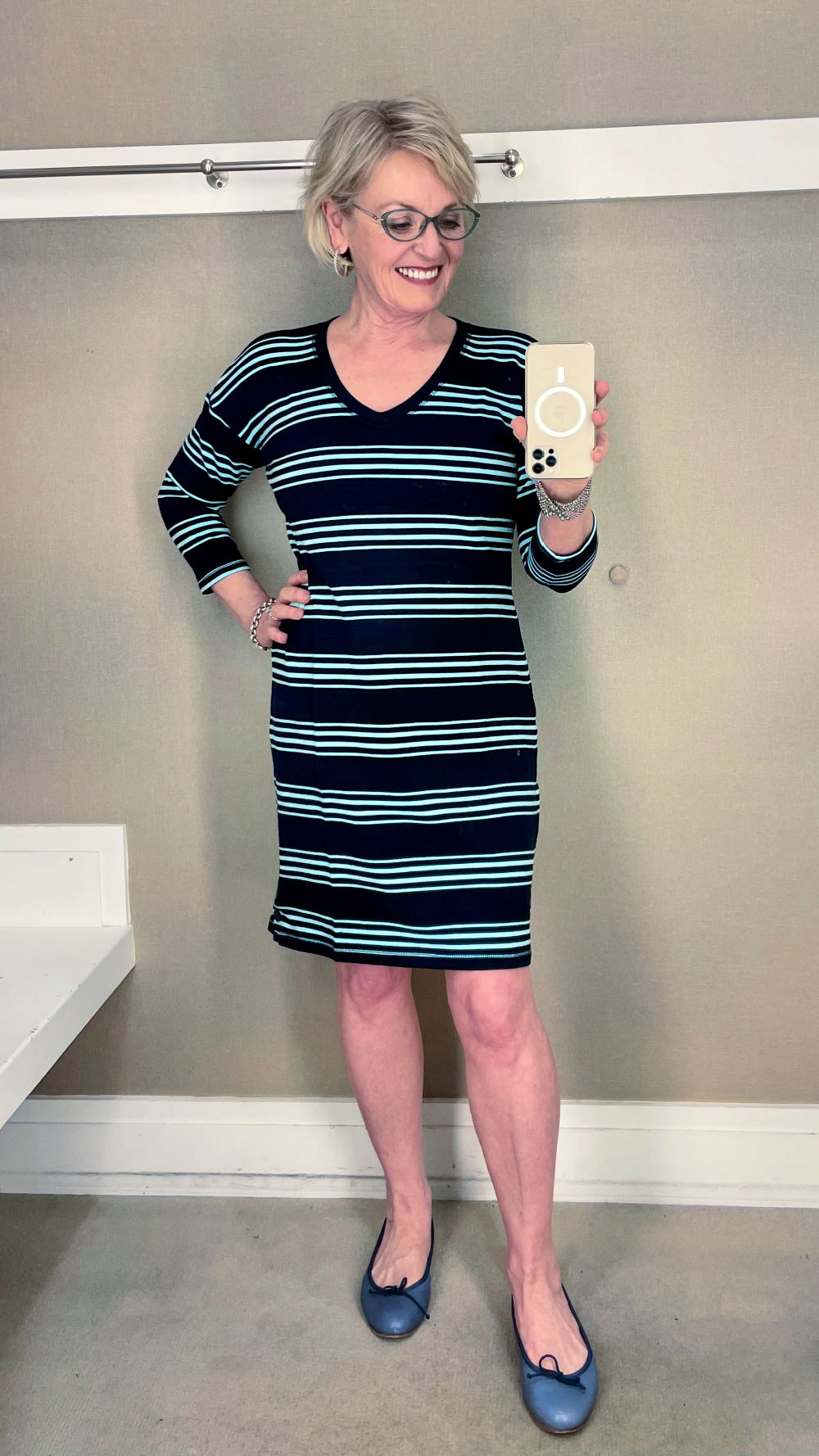 woman trying on striped dress in dressing room