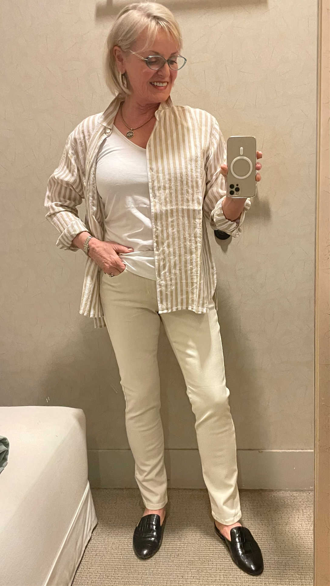 woman modeling striped shirt and jeans in dressing room selfie