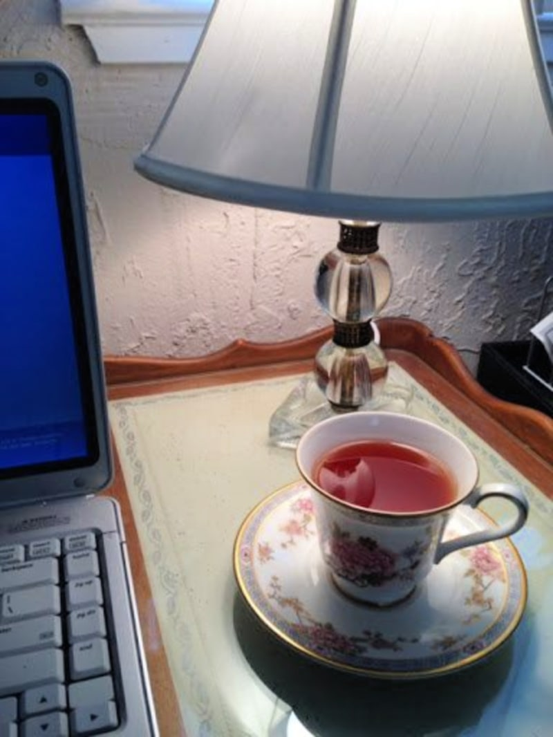 tea cup on desk next to laptop
