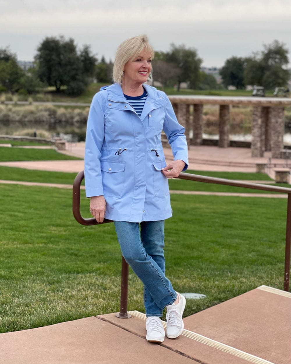woman leaning on railing wearing striped tee, blue jeans and coated canvas anorak