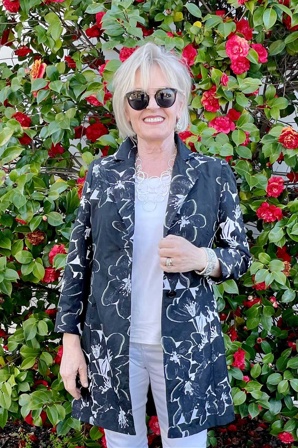 blonde woman wearing white and black floral jacket with white top