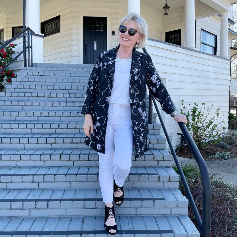woman coming down stairs in white jeans with black and white jacket