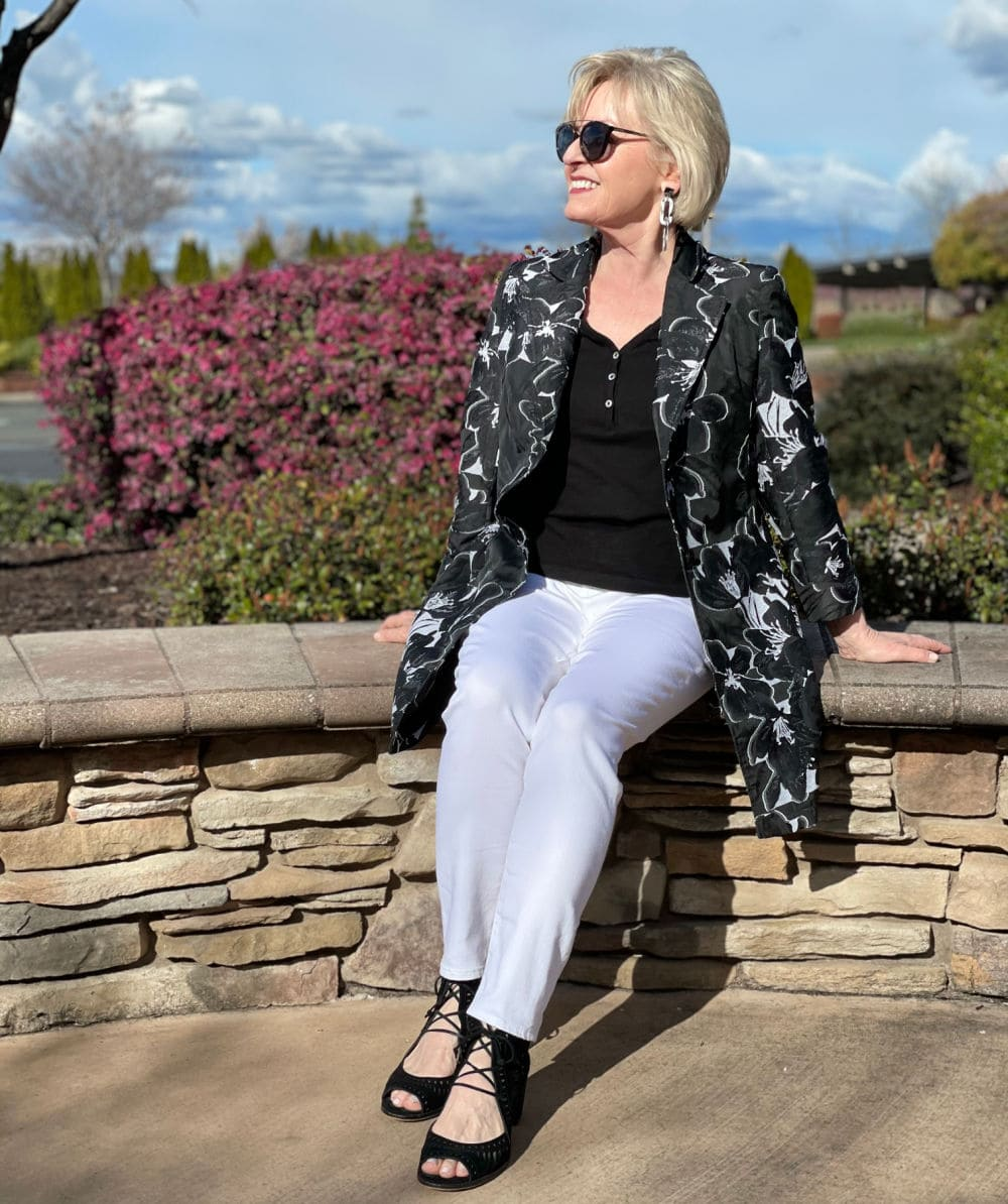 woman sitting on rock wall wearing white jeans, black top and white and black jacket