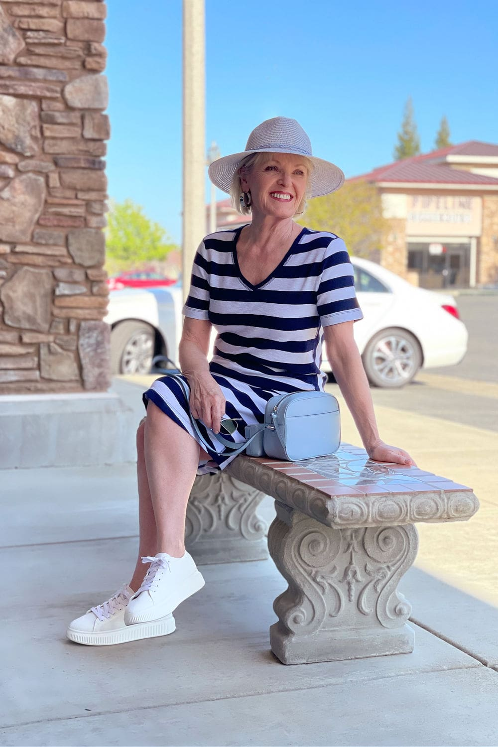 woman sitting on bench wearing white sneakers and athleisure striped tee dress