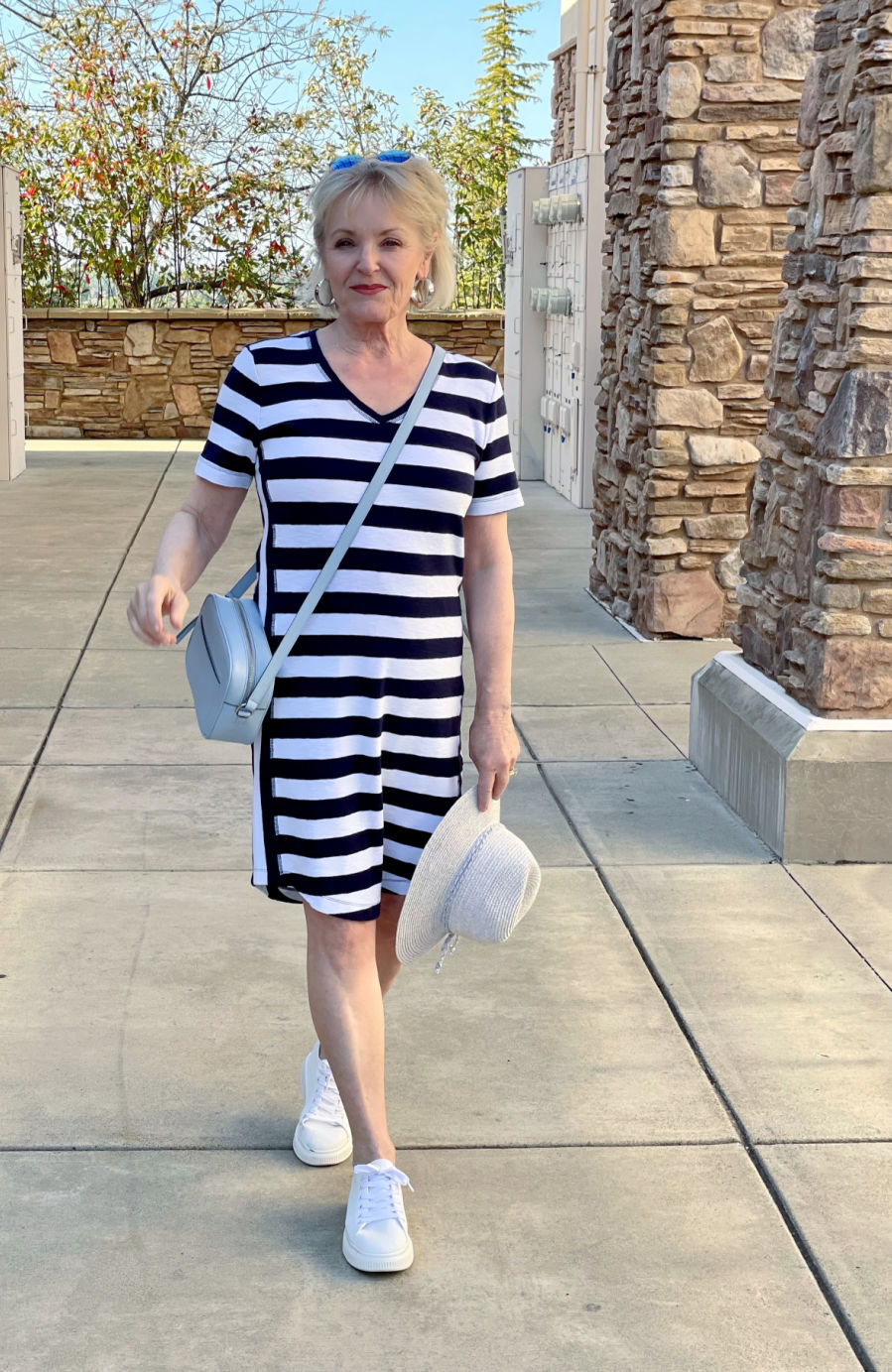 woman walking in navy and white striipe dress and white tennies