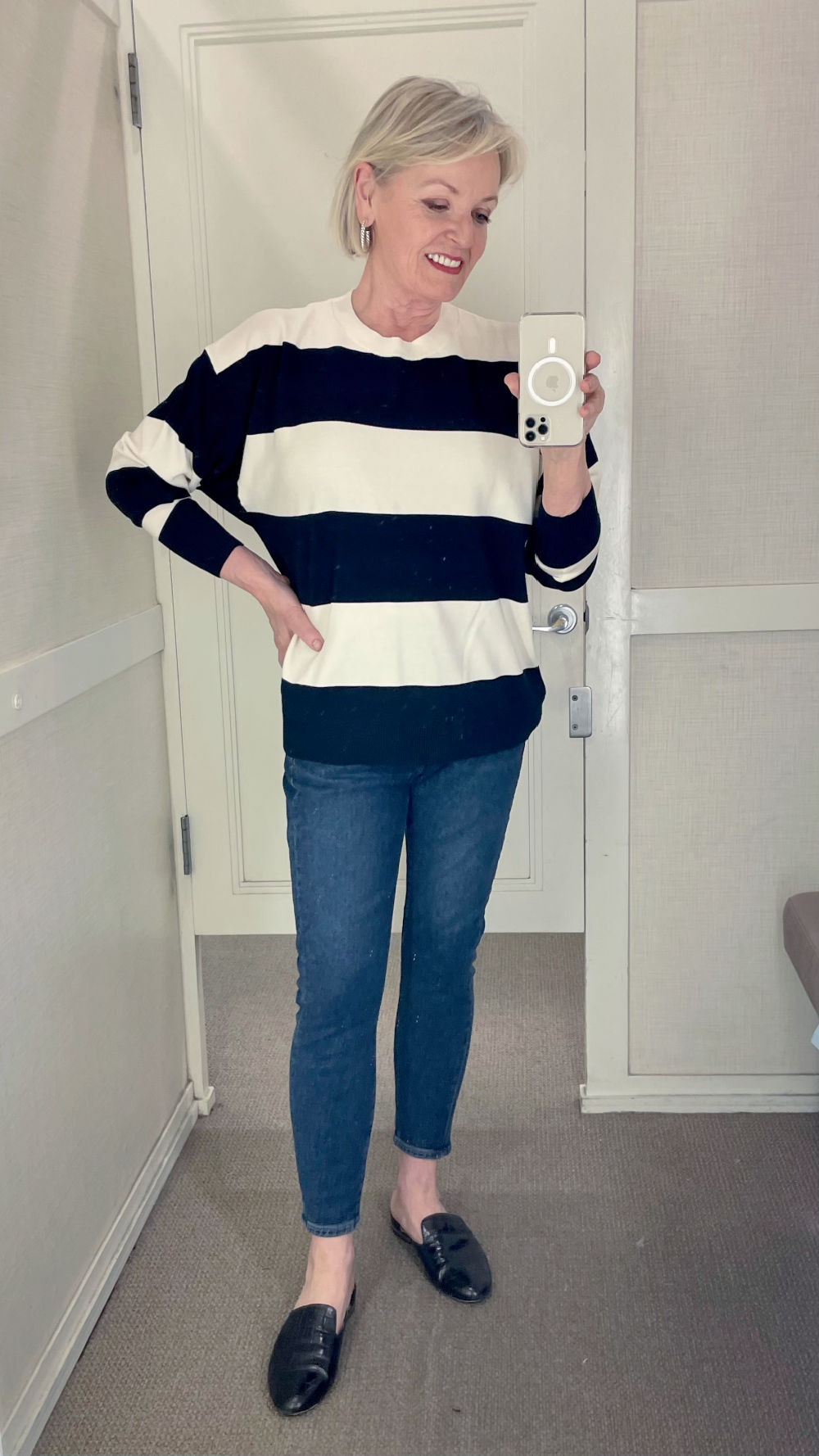 woman in Loft dressing room wearing striped sweater and skinny jeans