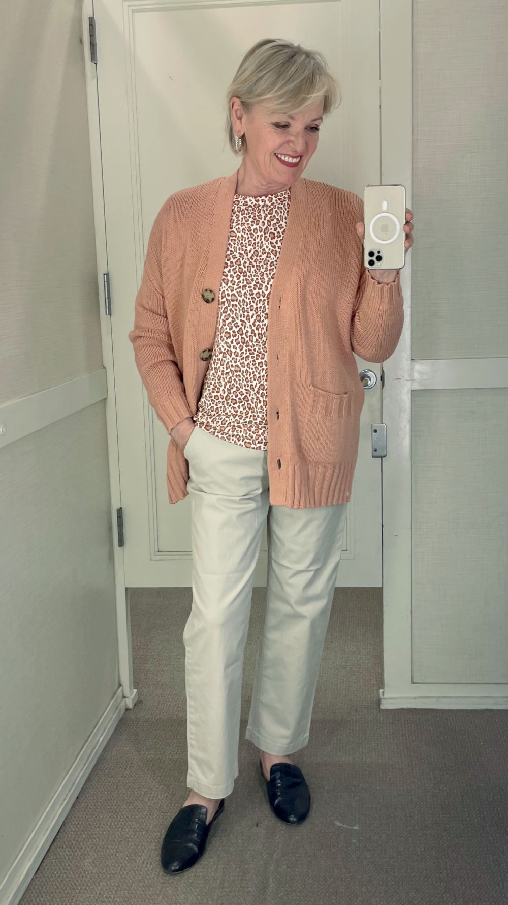 WOMAN WEARING LONG CARDIGAN AND CHINOS IN DRESSING ROOM