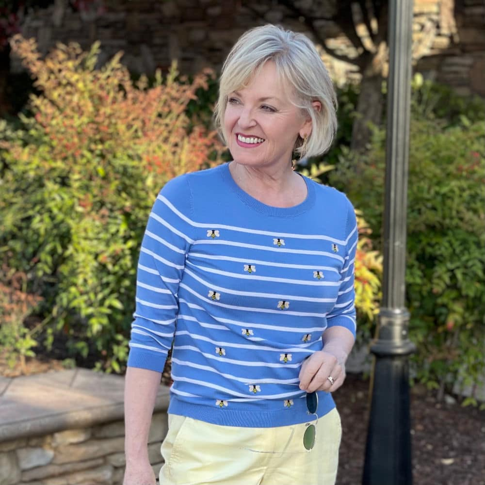 blonde woman wearing blue and white stripped sweater with bees on it