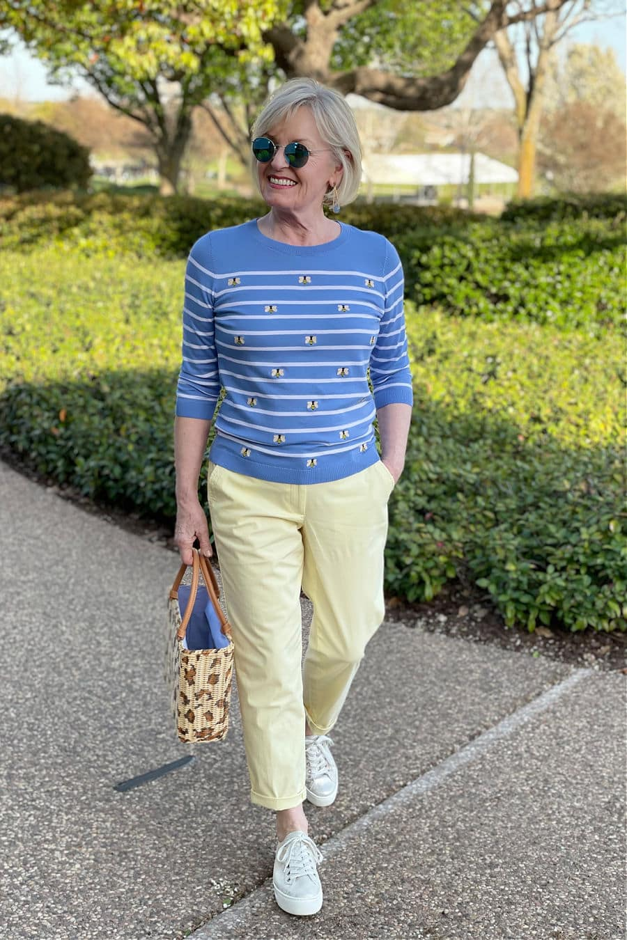 woman walking in park wearing spring outfit of blue striped sweater and yellow pants