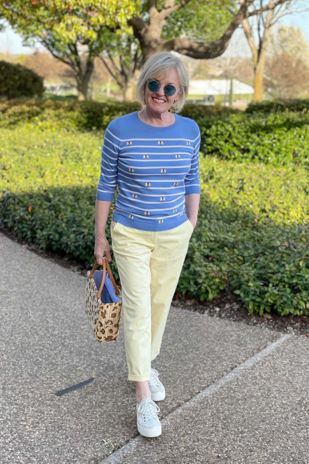 woman walking in blue sweater and casual chinos for spring