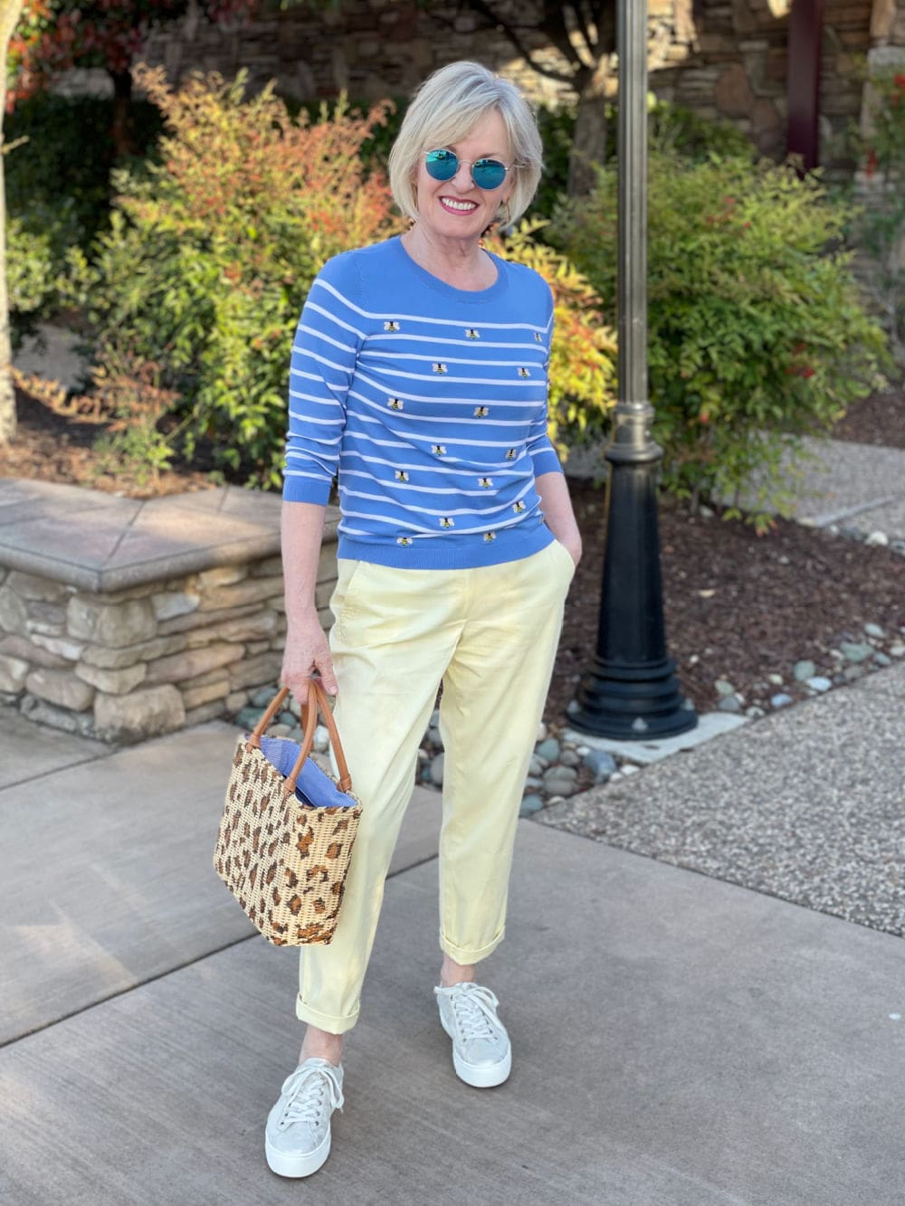 blonde woman wearong blue striped sweater with casual yellow chinos for spring day