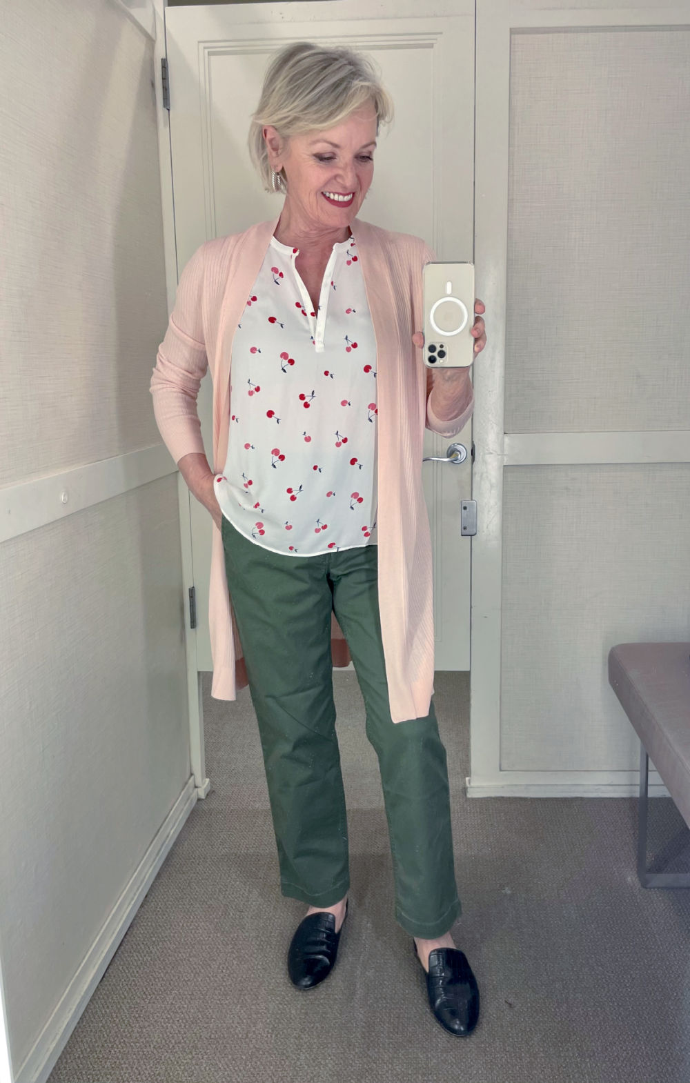 blond blogger wearing pink cardigan and top with chinos in dressing room at Loft