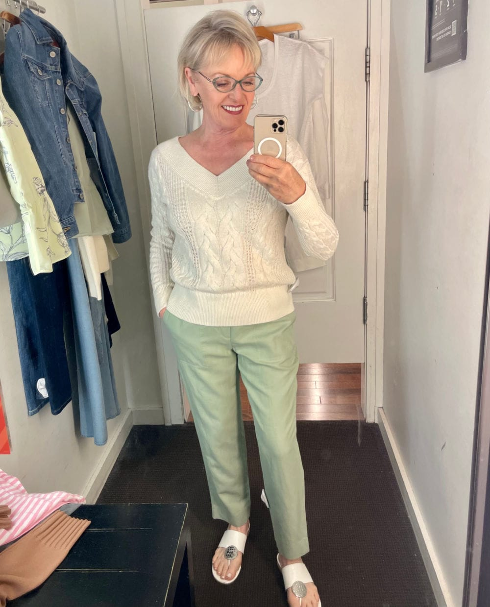 woman trying on green oants and ivory sweater in mirrror