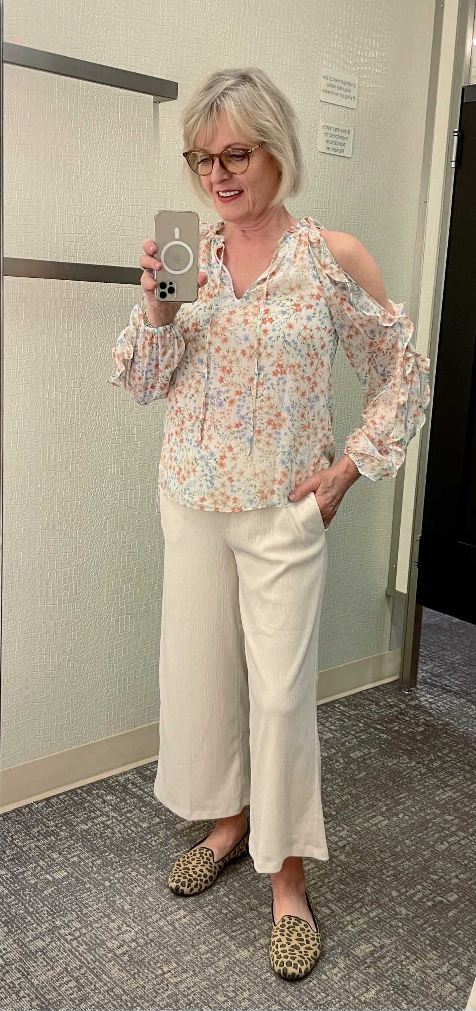 woman trying on crop pants and ruffle sleeve blouse in dressing room