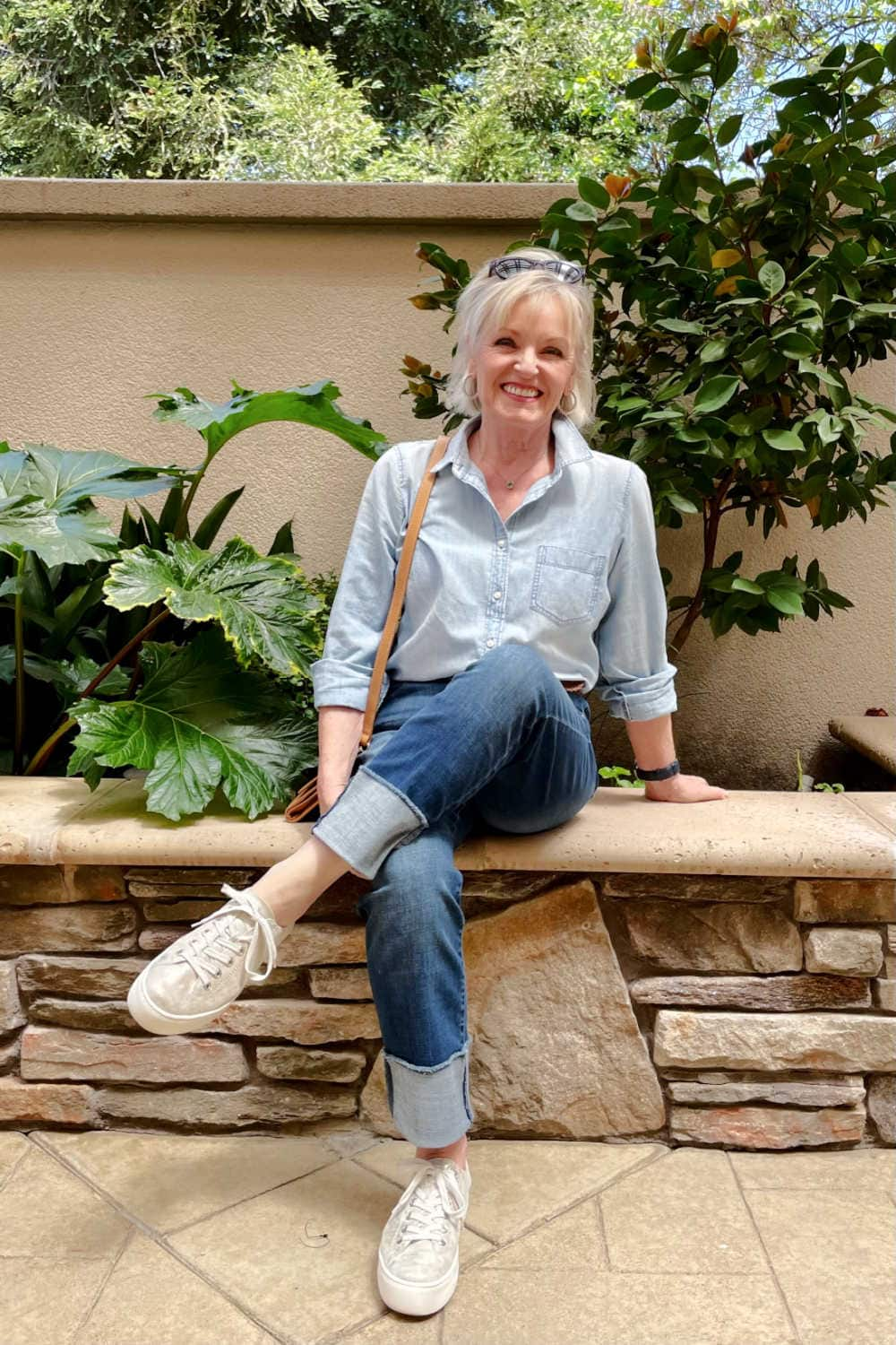 blonde woman sitting on wall wearing cuffed jeans, chambray shirt and gold sneakers