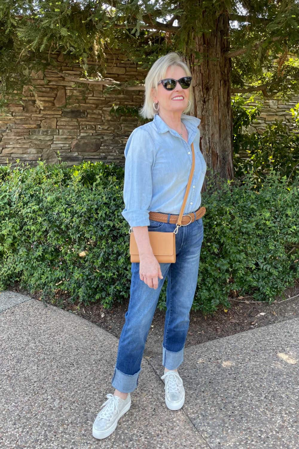 blonde woman weaing chambrays shirt, cuffed denim and gold sneakers standing in front of tree