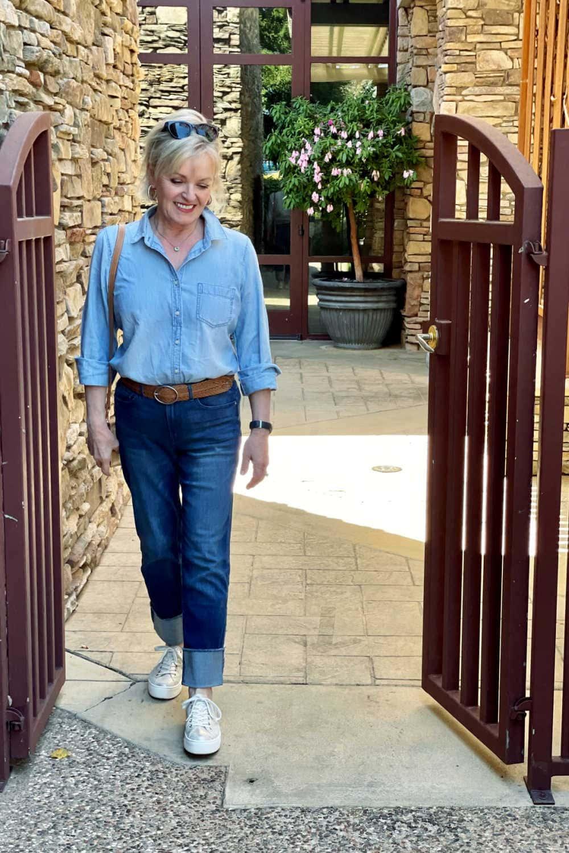 blonde woman walking through gate wearing cuffed denim and chambray shirt