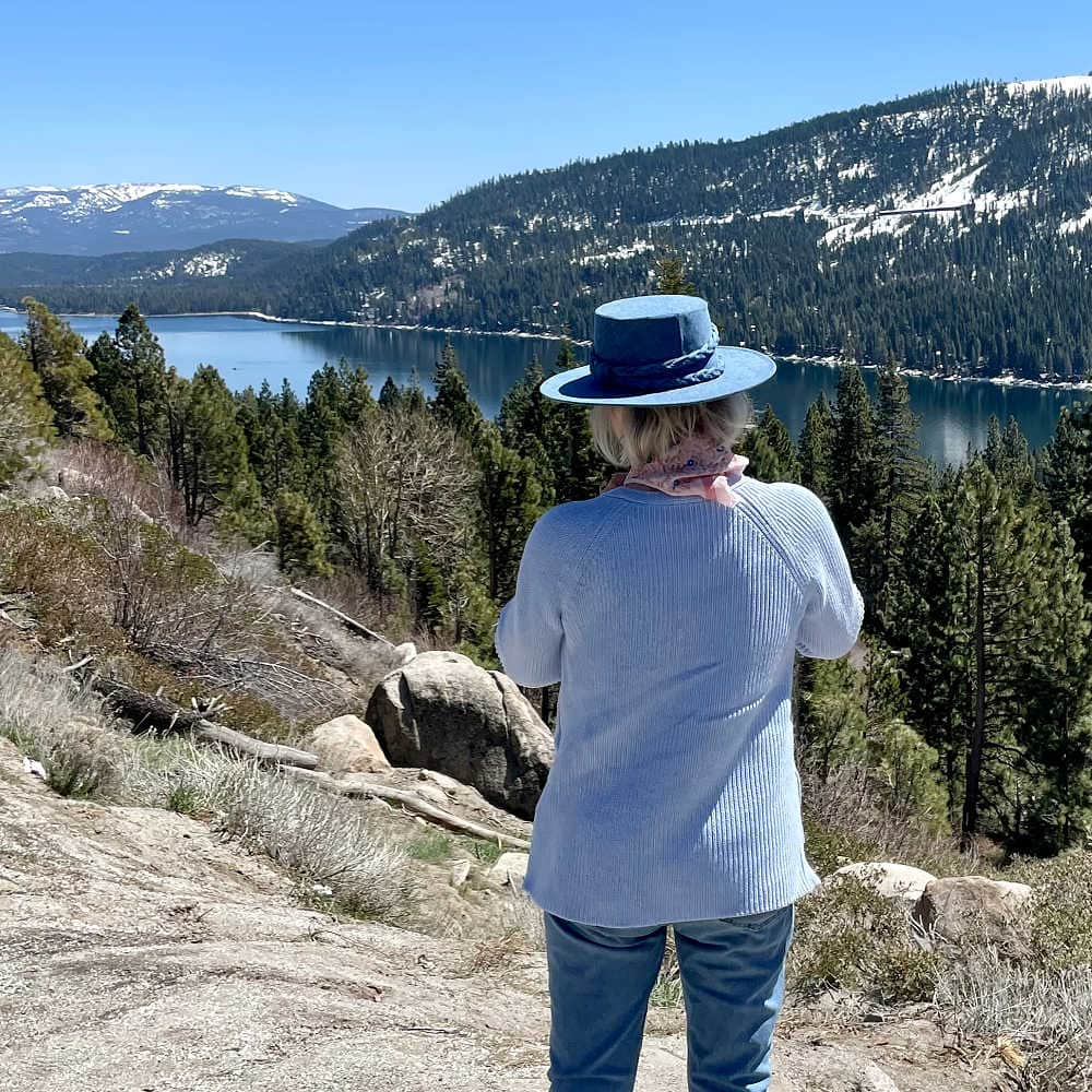 woman wearing denim hat and blue jeans looking over Donner Lake.