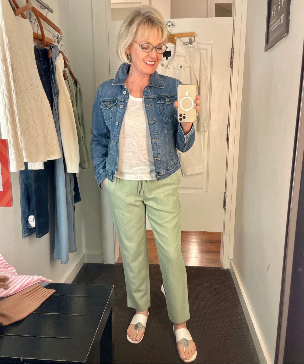 woman wearing white tee, green pants and denim jacket in dressing room