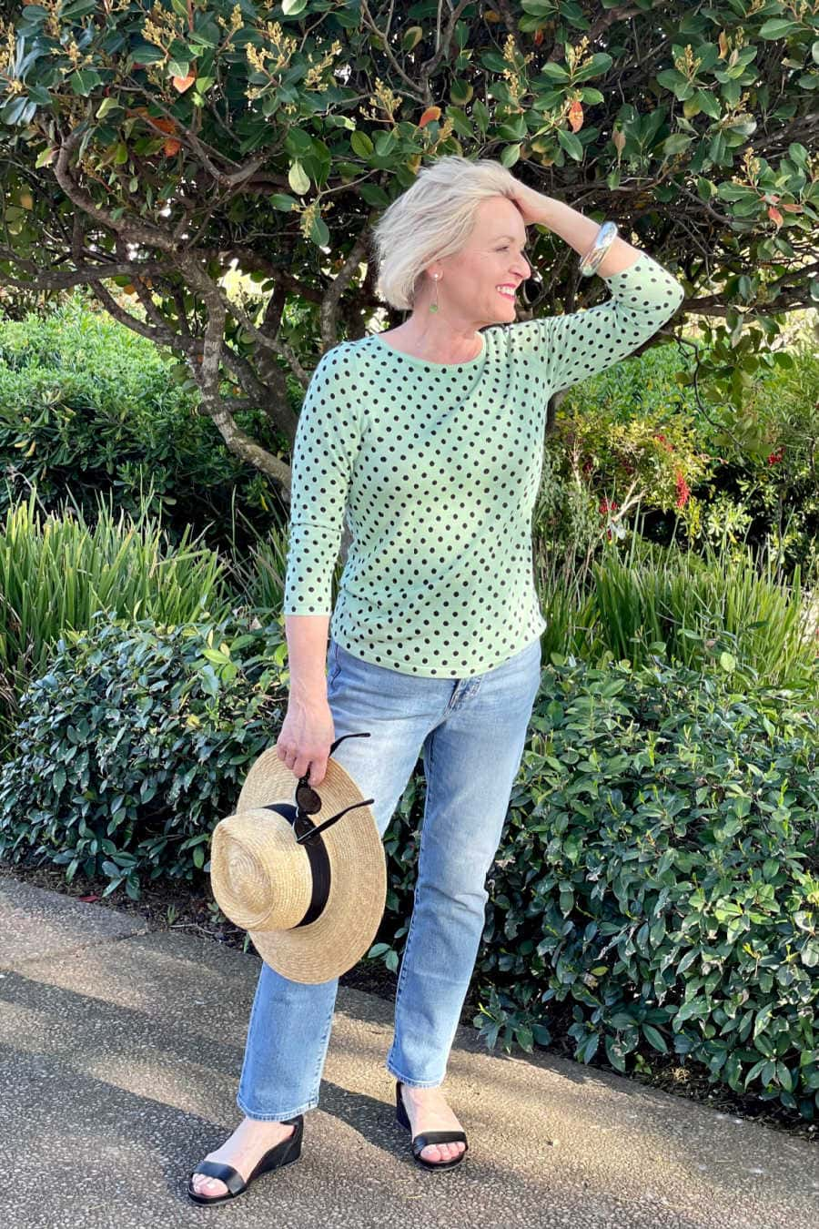 middle age woman wearing pale blue jeans and green polka dot sweater
