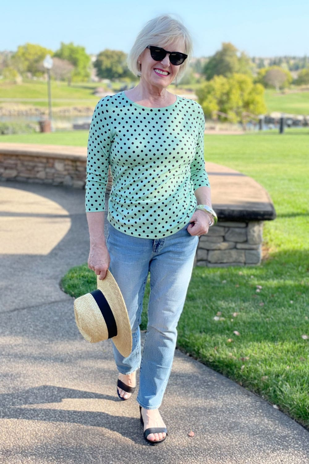 woman walking on path wearing causal green polka dots