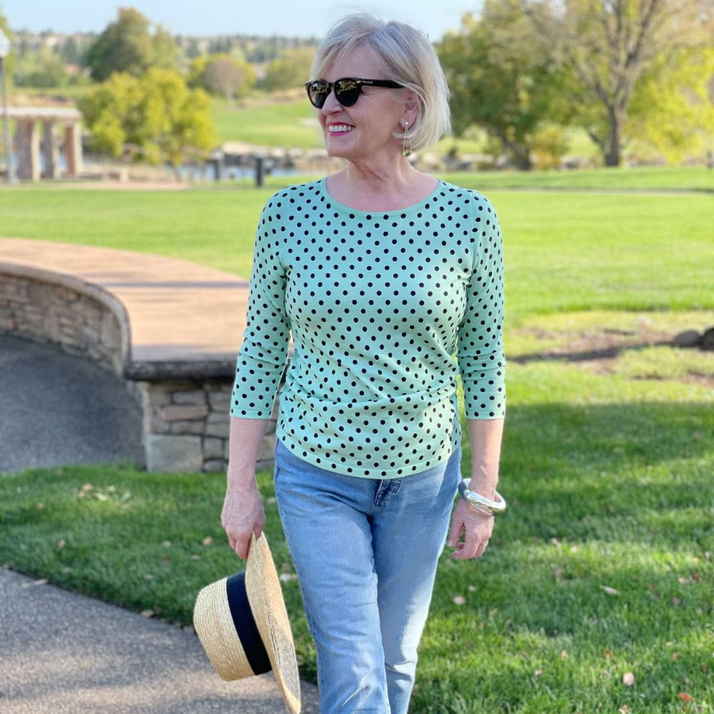 woman wearing green polka dot sweater and bue jeans
