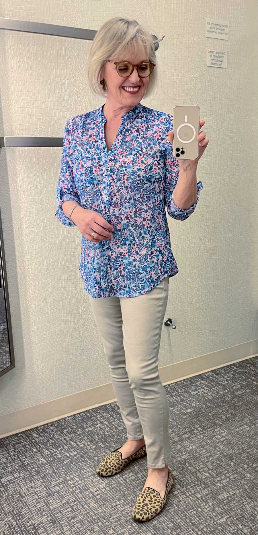 blonde woman taking picture in mirror of her wearing floral blouse and tan jeans
