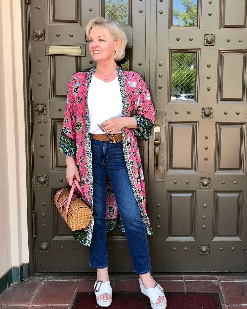 woman standing in front of green door wearing floral kimono and blue jeans