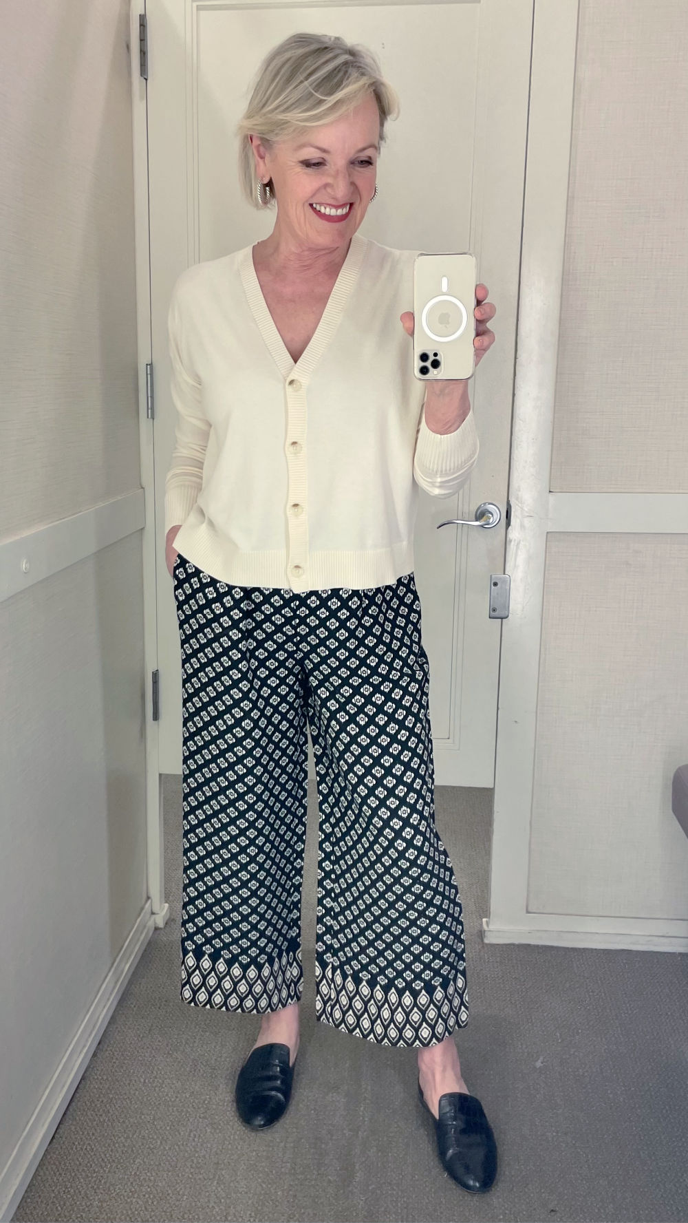 woman trying on cardrigan and print pants in dressing room with spring fashion at loft