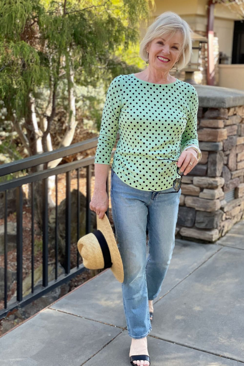 woman walking near fountain wearing green sweater and blue jeans