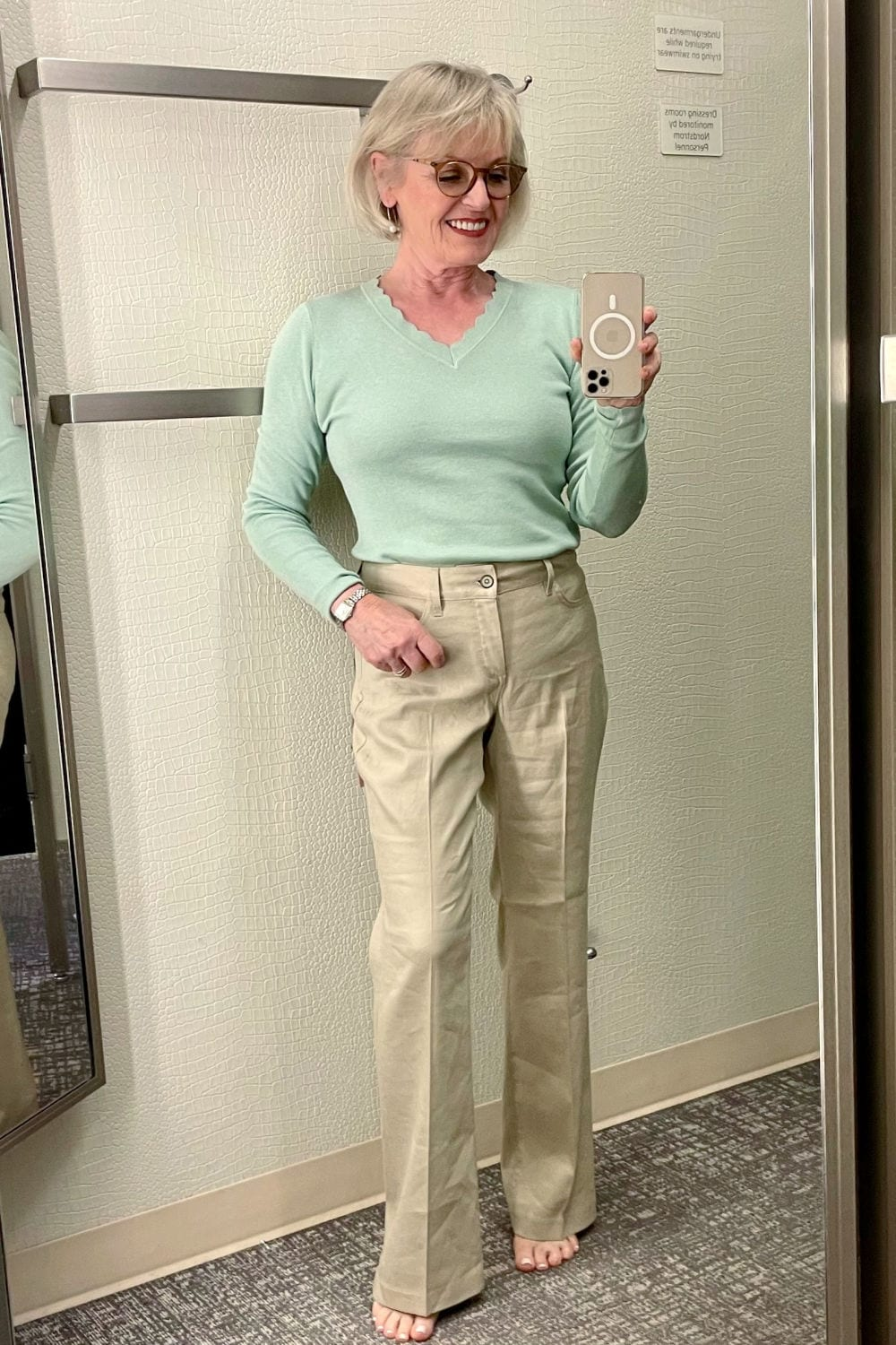 blonde woman in dressing room trying on green sweater and beige linen pants