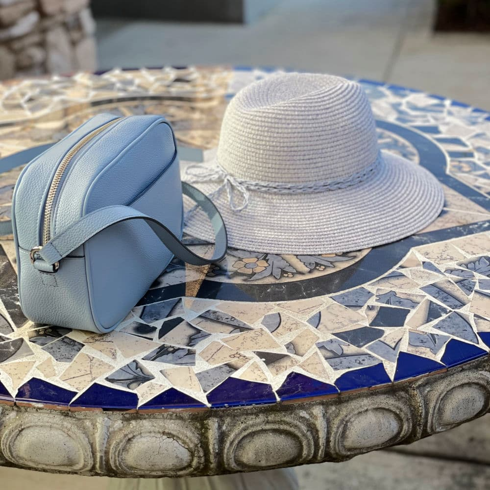 blue cross body bag and blue straw hat on table