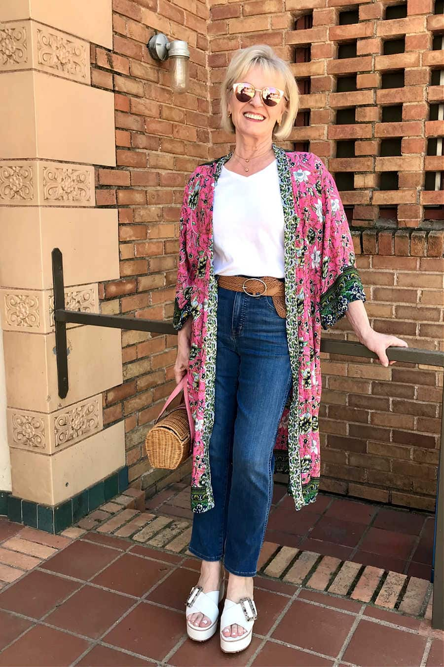 blonde blogger wearing pink kimono with stovepipe blue jeans and white wedge sandals