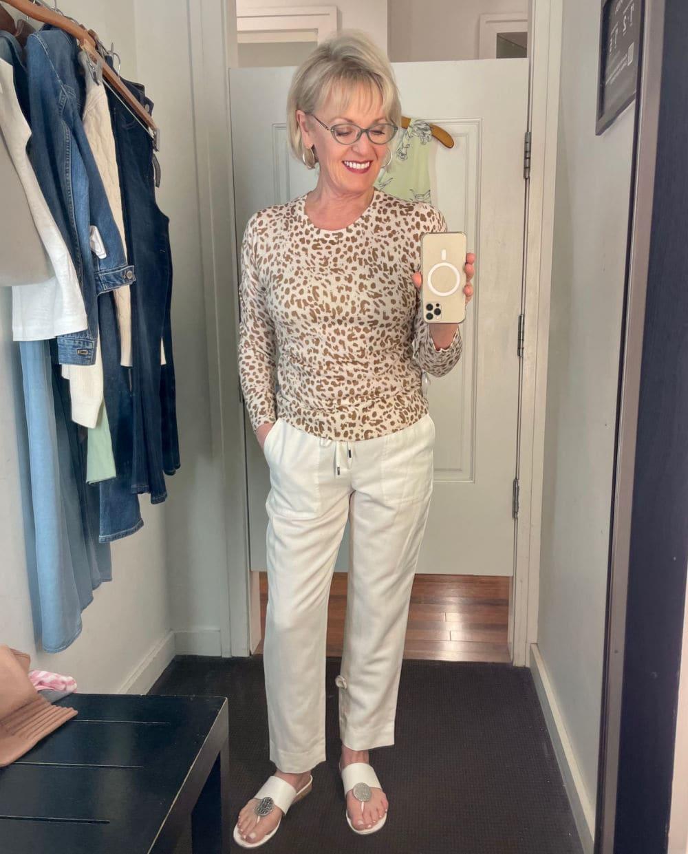 blonde woman wearing banana republic leopard sweater and white pants