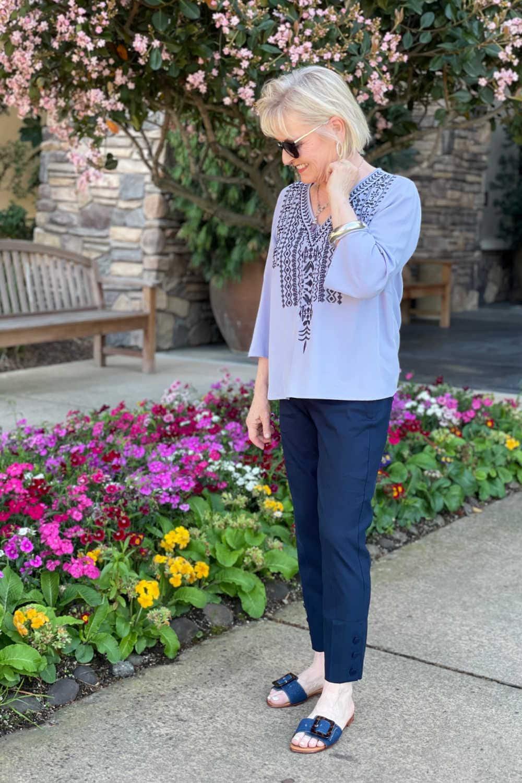 blonde woman wearing navy linenb pants anmd boho top in flower garden