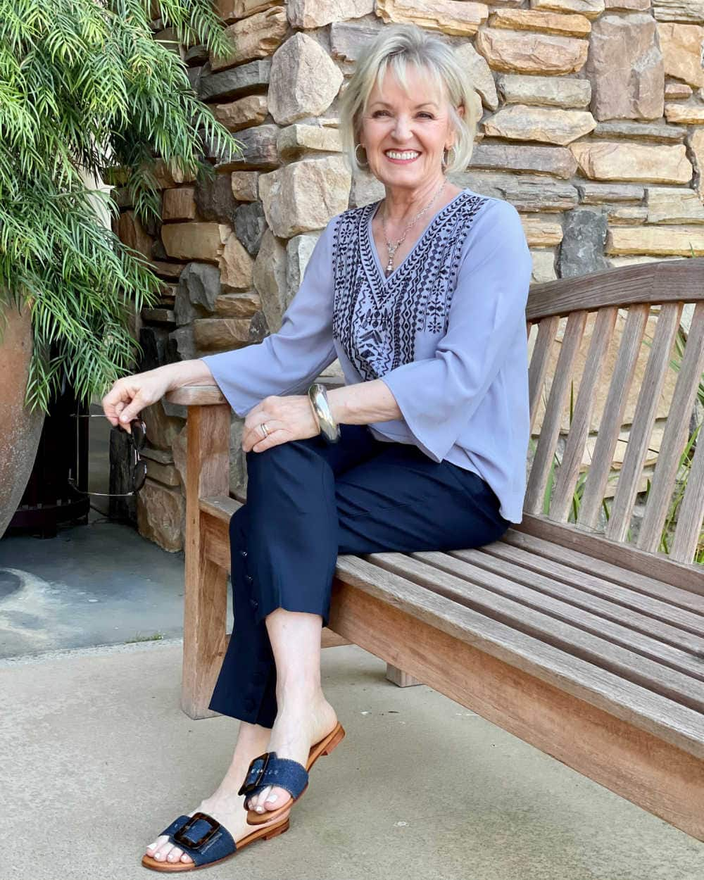 woman sitting on park bench wearing linen pants boho top and denim shoes