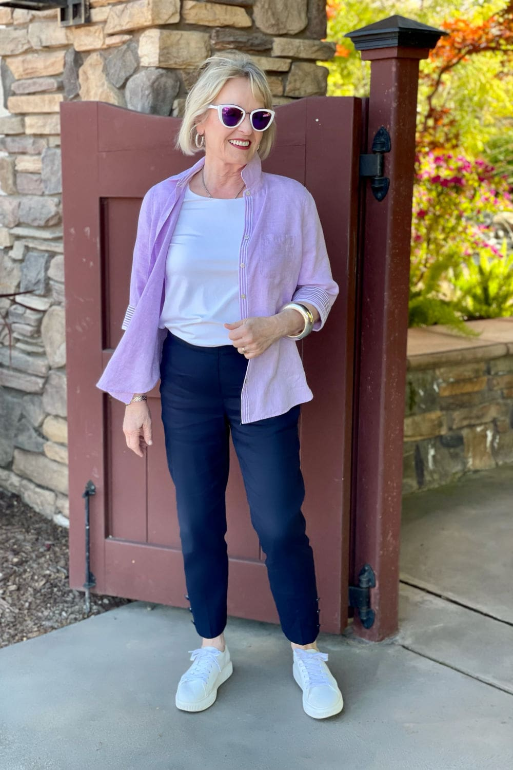 jennifer of a well styled life wearing linen shirt, linen pants and white sneakers with purple sunglasses
