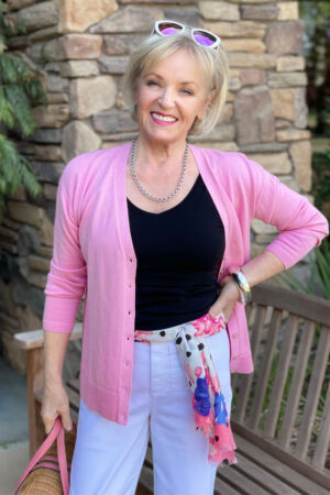 woman wearing scarf as belt with pink sweater and white pants
