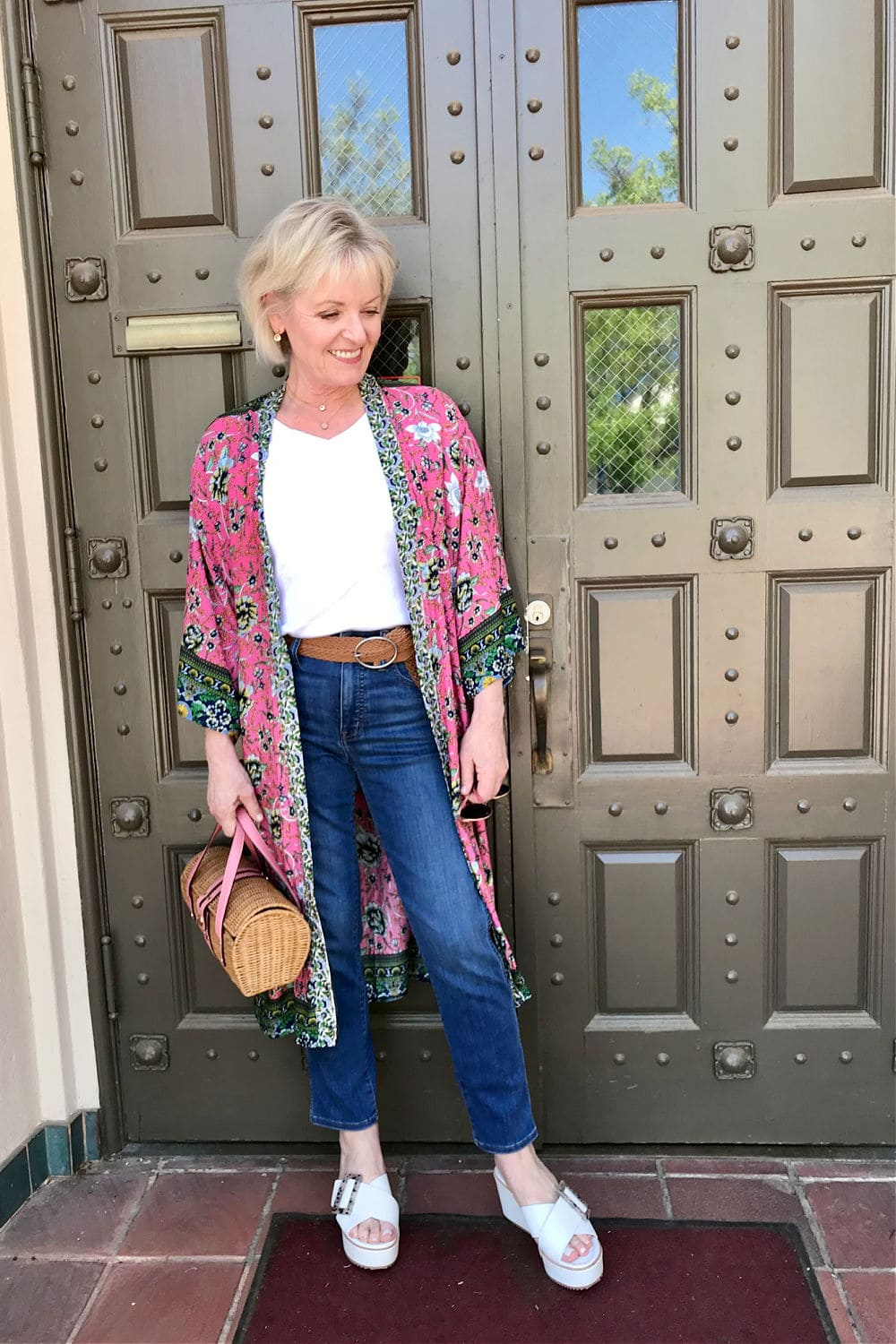 blonde woman wearing pink kimono ovr white tee and blue jeans