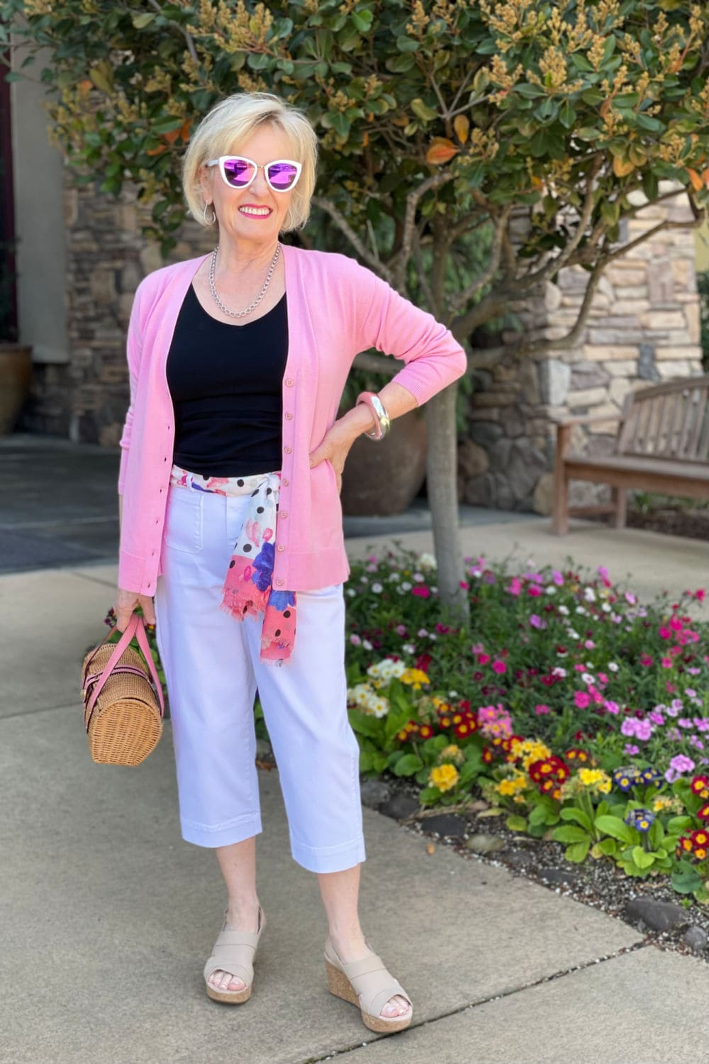 woman standing by flower garden wearing crop pants and bright pink cardigan