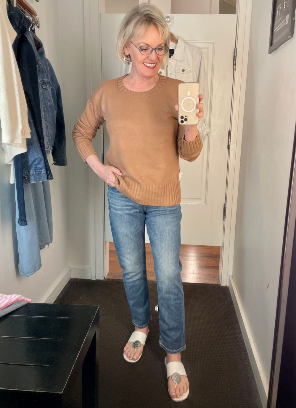 woman in dressing room trying on camel sweater and blue jeans