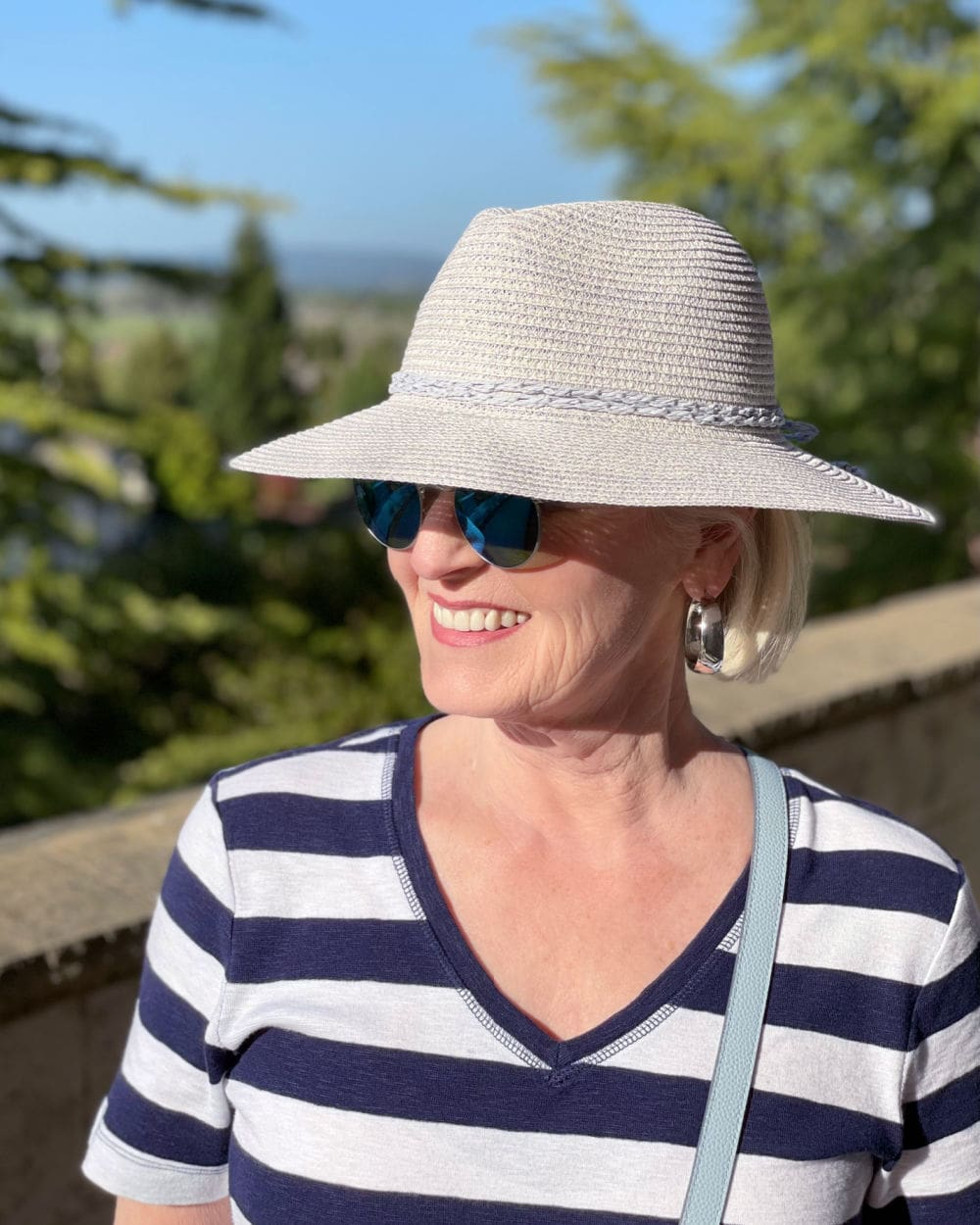 woman wearing straw hat and striped dress with sunglasses