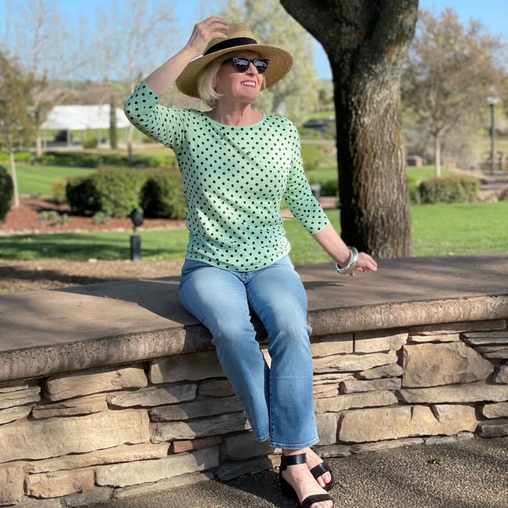 woman wearing straw hat and green polka dot sweater