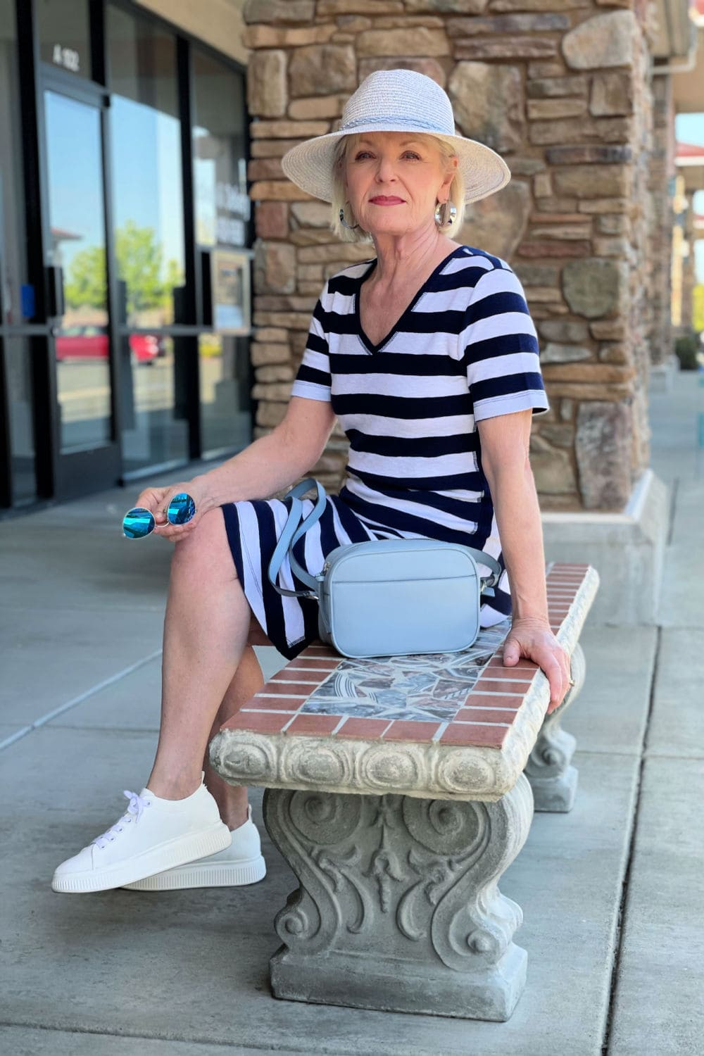 blonde woman sitting on bench wearing striped dress and straw hat