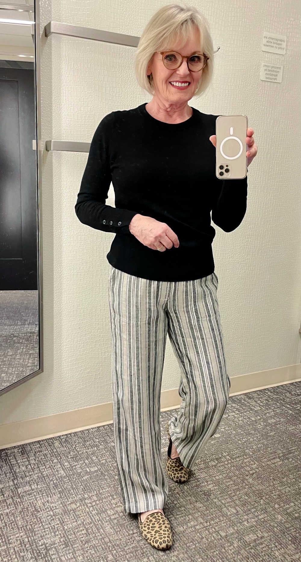 woman taking selfie in mirror wearing black sweater and striped linen pants