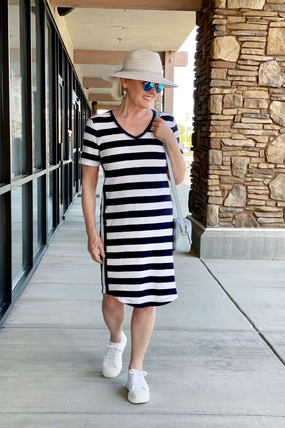 over 50 fashion blogger wearing striped tee dress and straw hat