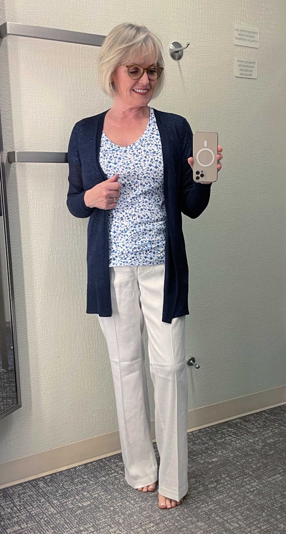 blonde woman wearing white linen pants and navy cardigan