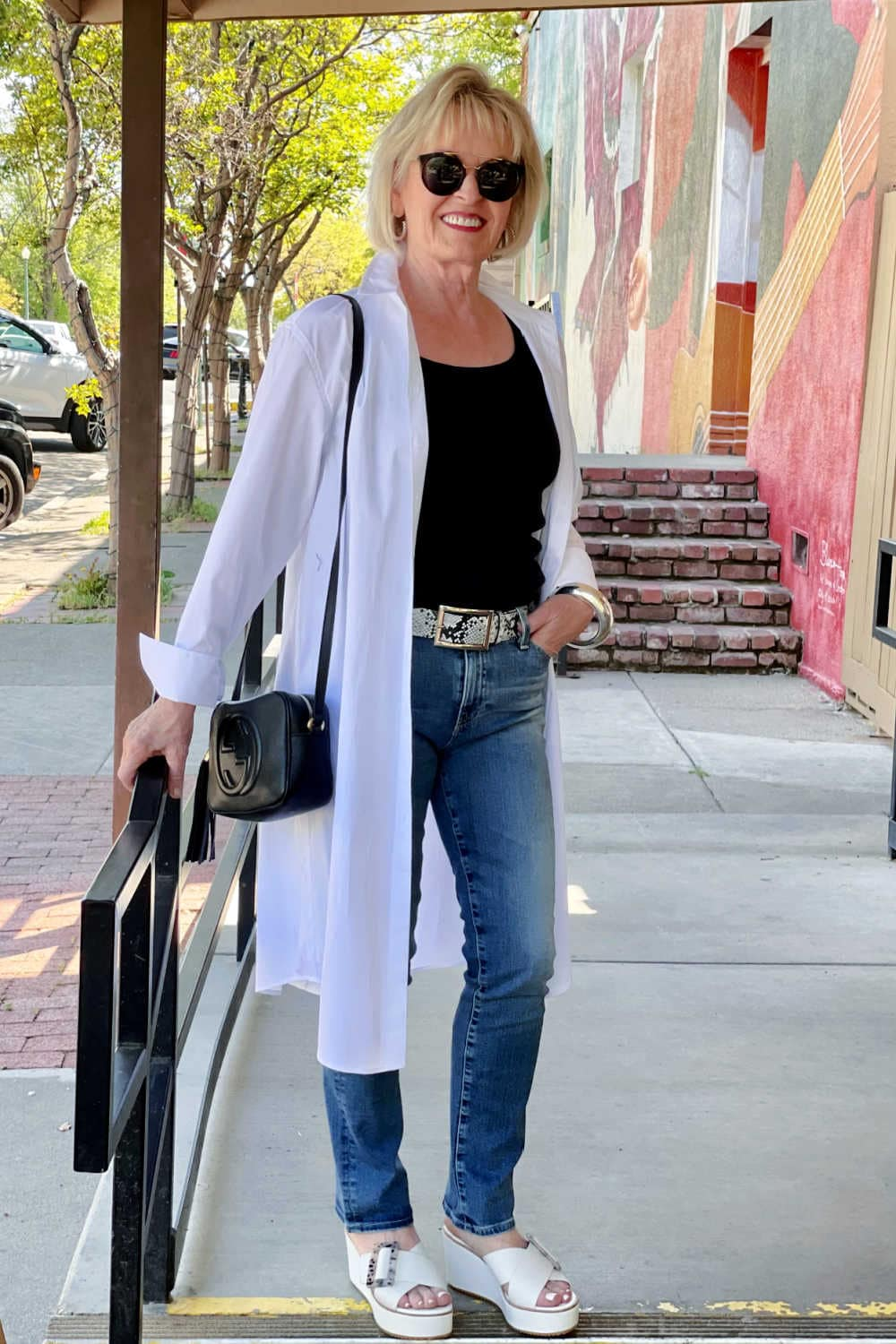woman in white duster and blue jeans on steps